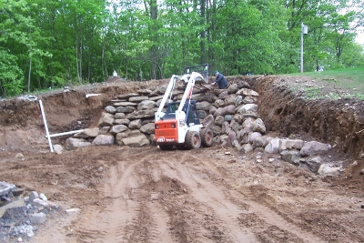 Skid steer with pallet forks building stone wall
